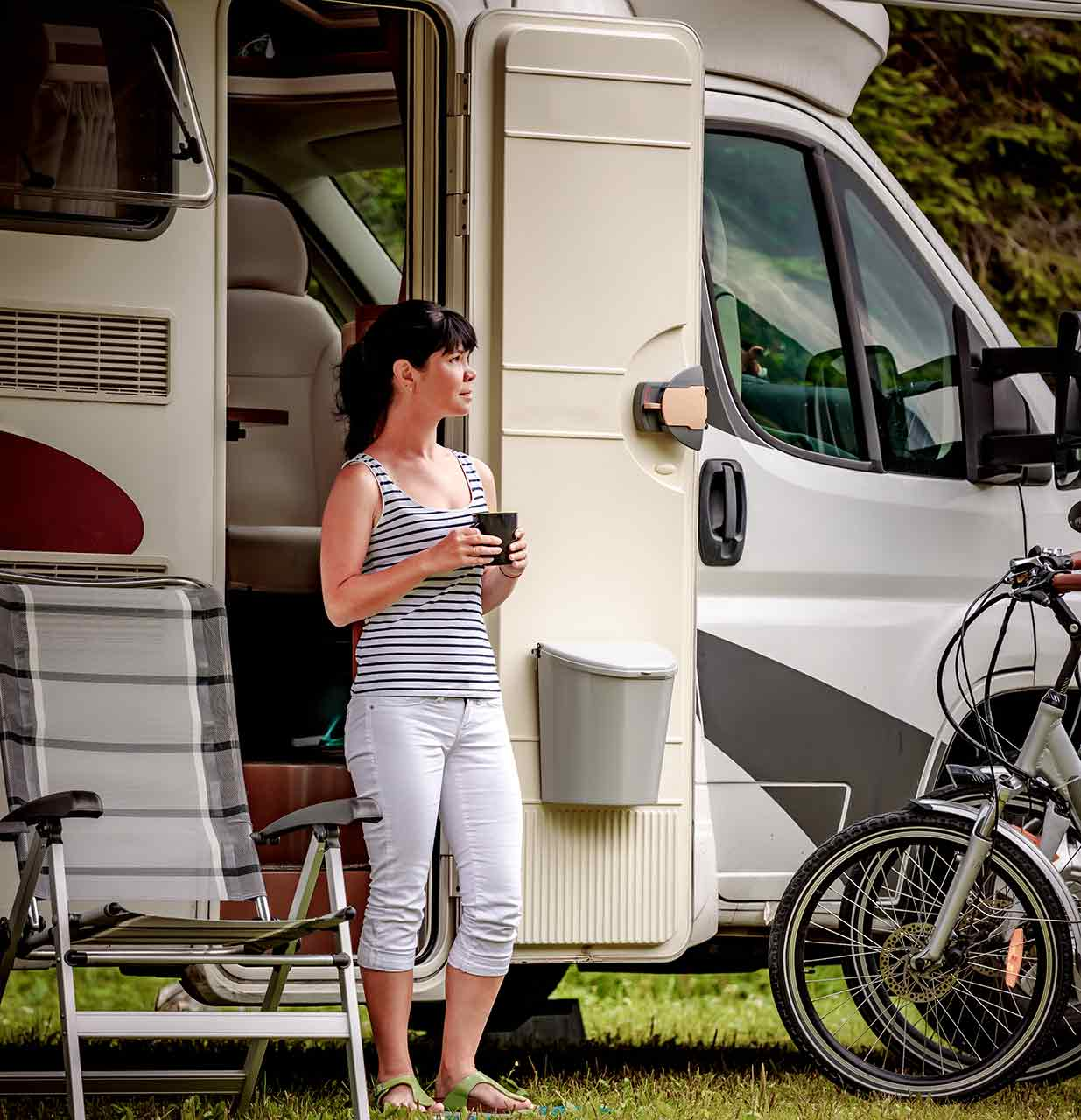 woman having coffee in front of RV