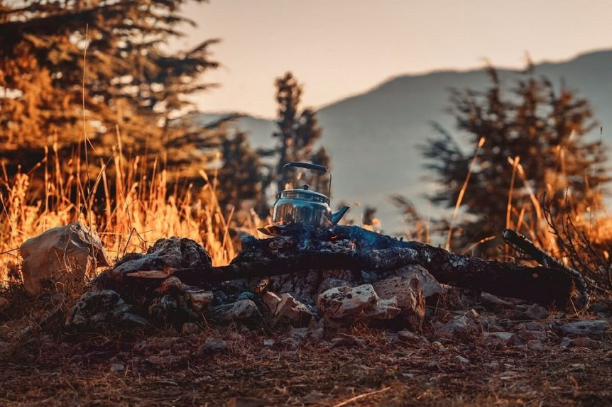 Teapot resting over campfire